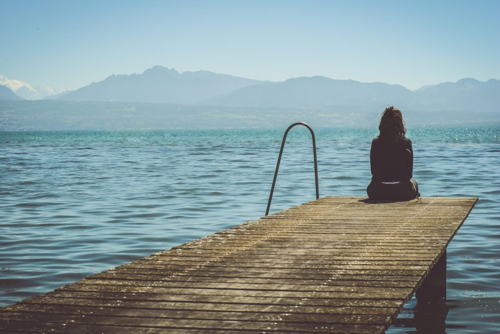 Photo of a desolate scene of a woman sitting on the edge of a dock looking out across a lake