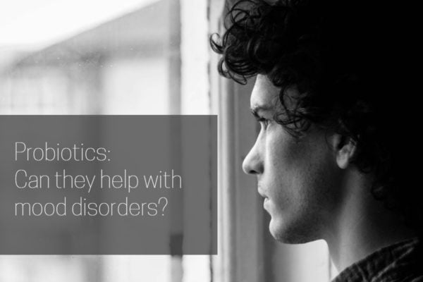 Cover image for article on probiotics and moo disorders with a young man looking out a window in black and white