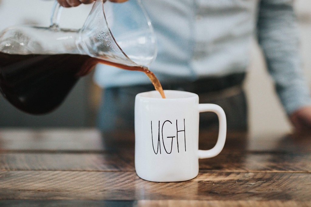 Image of a barista pouring coffee into a coffee mug that says'UGH'