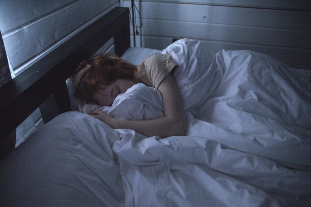 Image of a fatigued woman laying down curled up in blankets