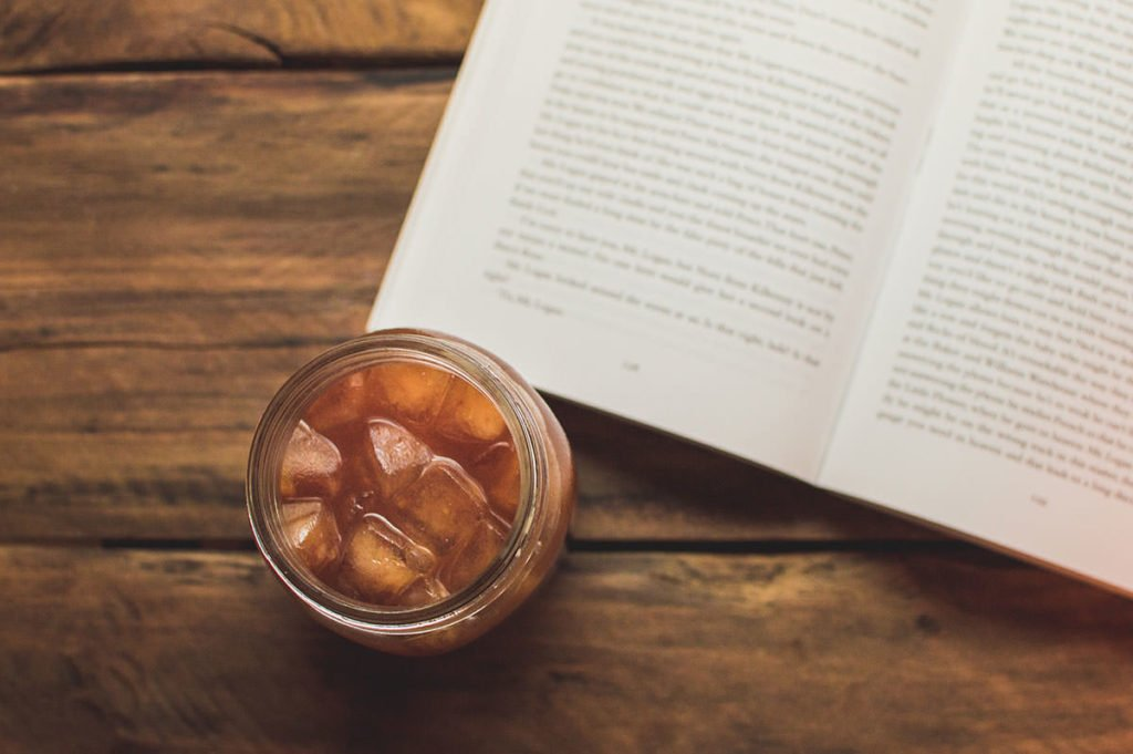 Image of kombucha tea on a wooden table next to a book from above