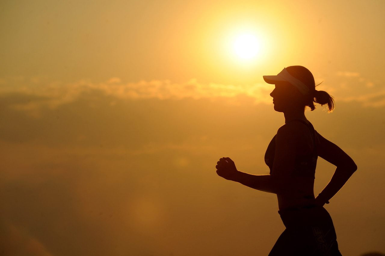 Image of a woman running in front of the sun setting
