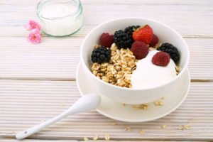 Image of yogurt, fruit and granola in a bowl on a table, which can contain the probiotic lactobacillus rhamnosus