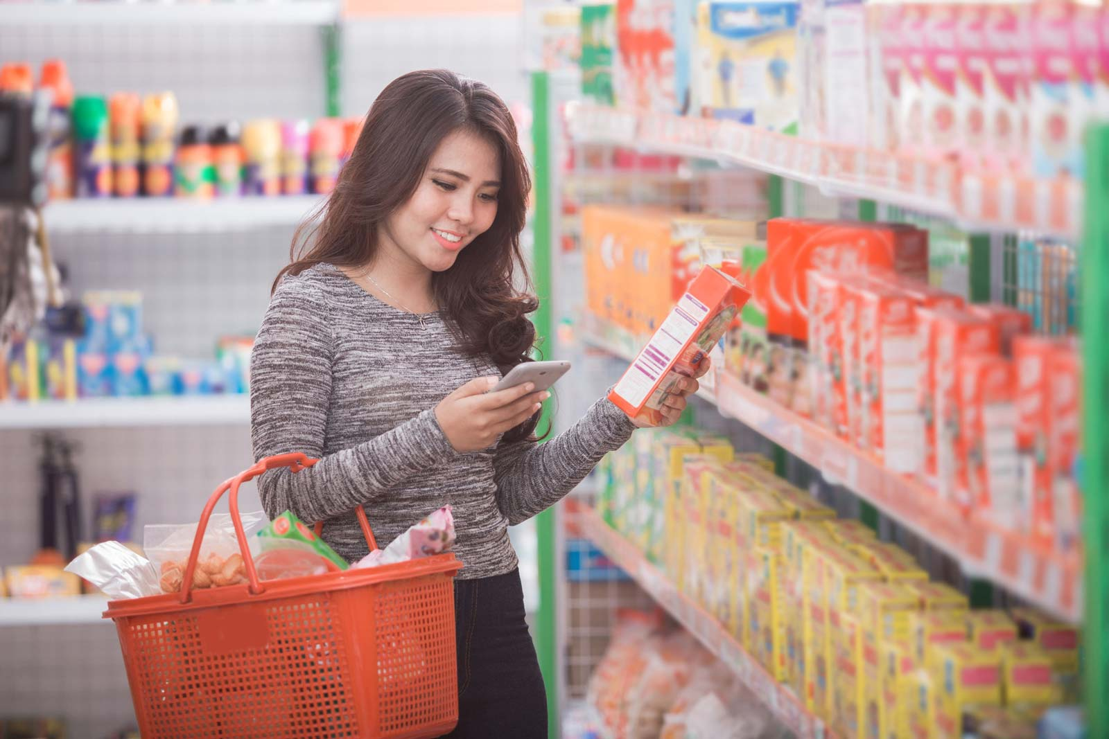 Image of a woman reading a nutrition label in a grocery store
