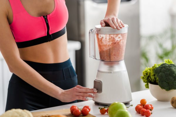 Photo of a woman in athletic wear blending a nutritional smoothie