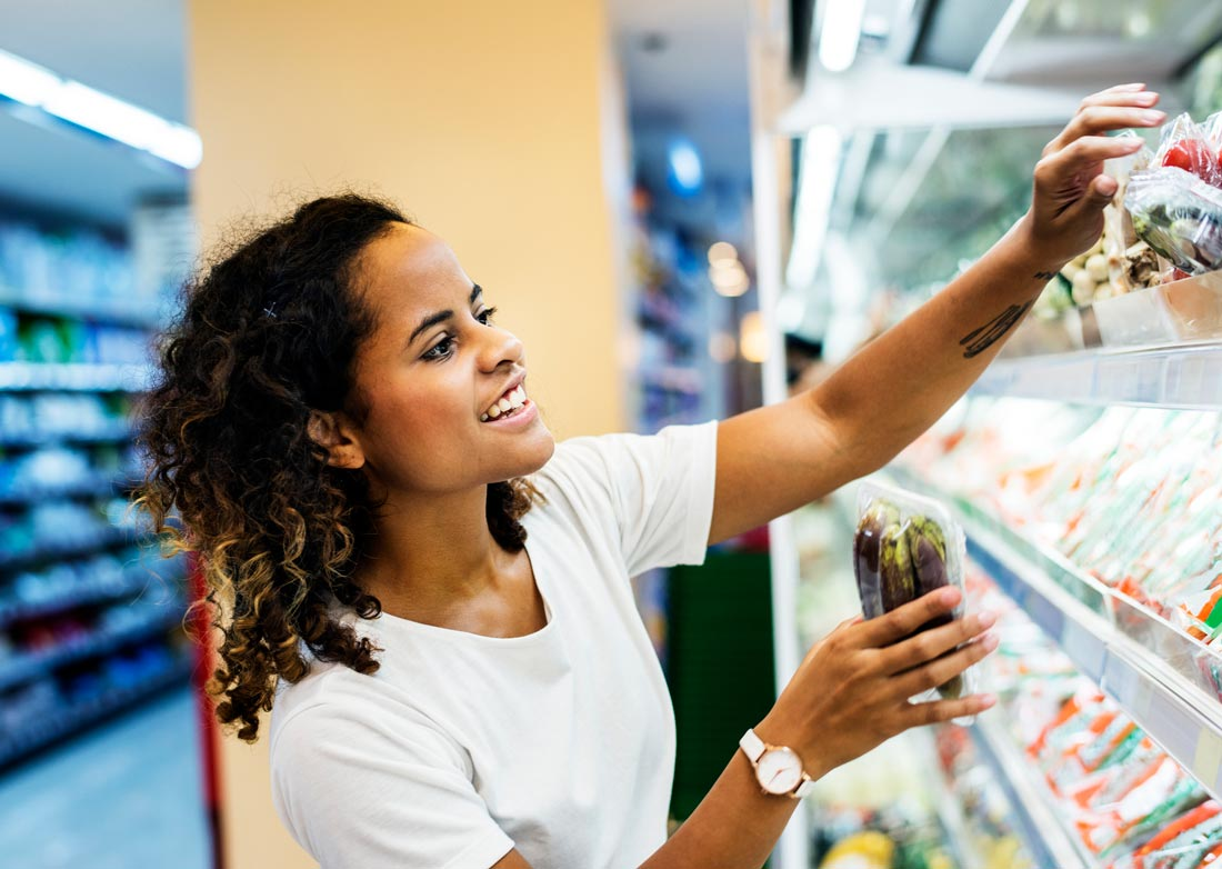 Image of a woman shopping at a grocery store for DASH diet and Mediterranean diet food