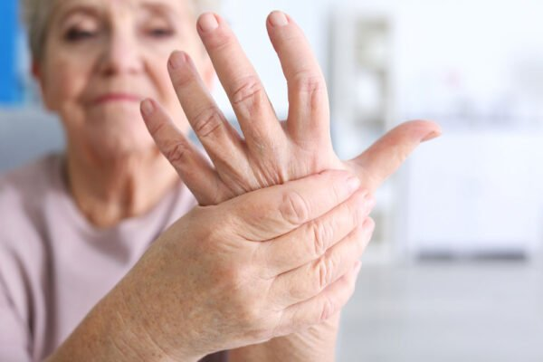 Image of a senior woman holding her hand with arthritis pain