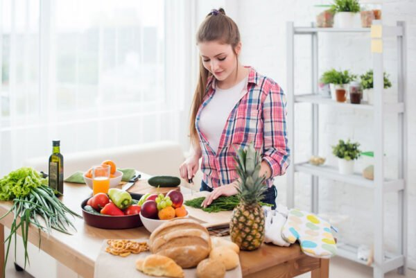 Image of a woman preparing a meal rich in digestive enzymes